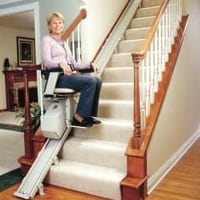 woman ascending stairs riding a stair lift at home
